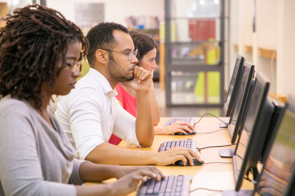 Multiracial group of students training in computer class